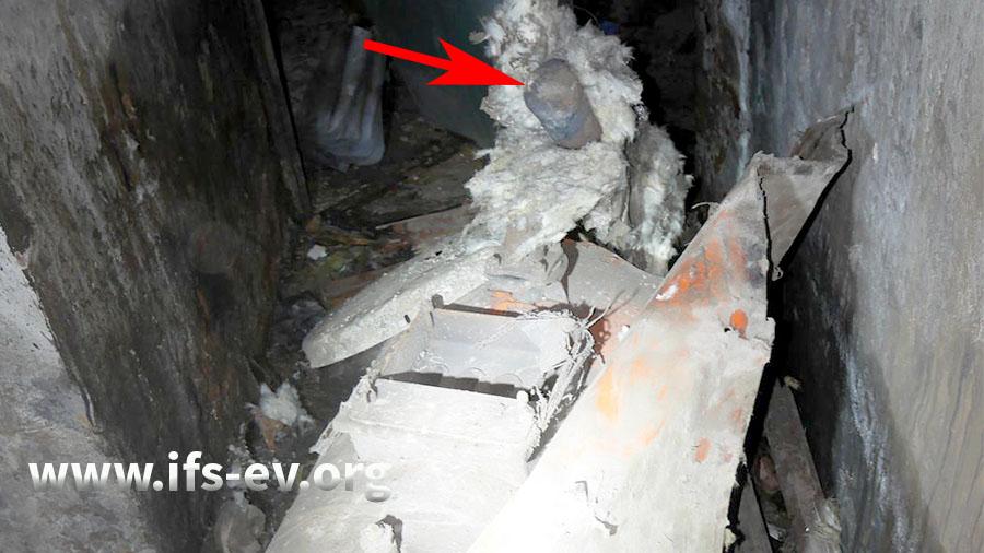 Blick auf den Kessel: Die Außenhülle aus Blech ist aufgerissen. Oben ist ein abgerissenes Anschlussrohr zu erkennen (Pfeil).