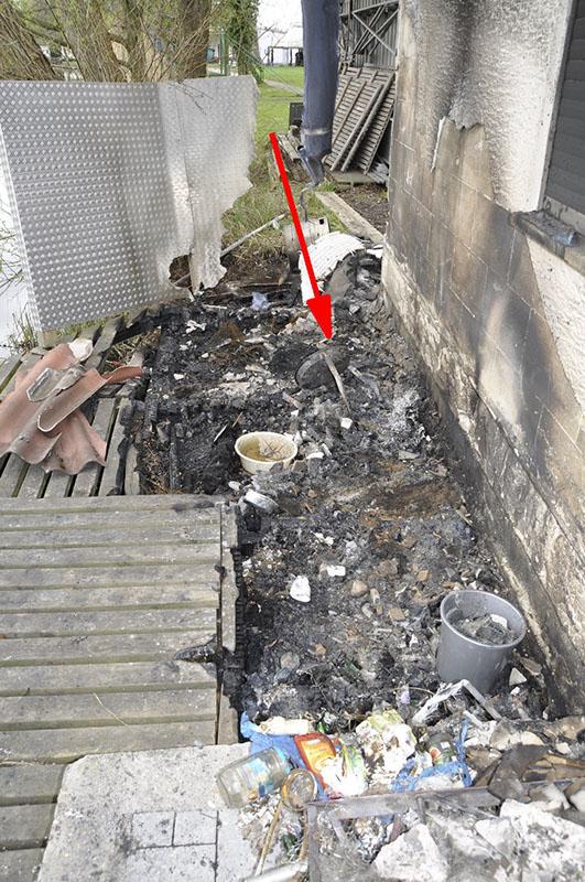 Im Brandschutt liegt ein Holzkohlegrill (Pfeil).