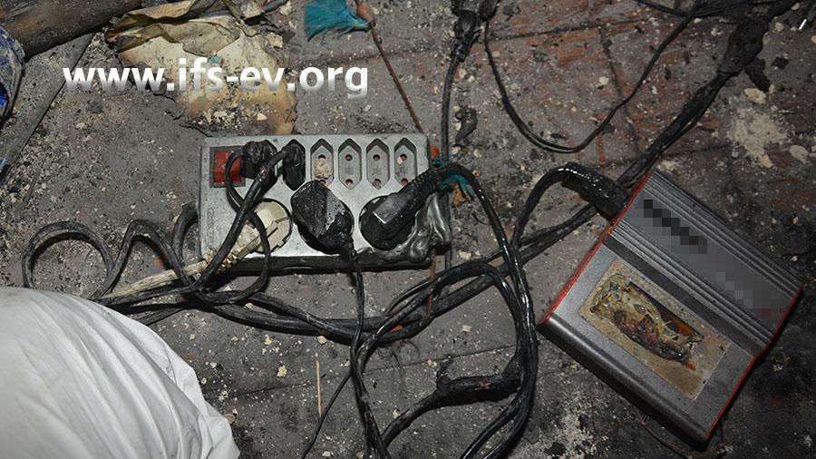 Im Brandbereich wird ein gut erhaltenes Ladegerät gefunden, das an eine Mehrfachsteckdose angeschlossen ist.