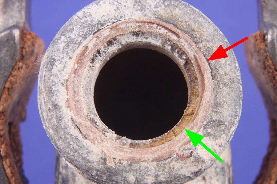 Blick auf die Bruchfläche des abgebrochenen, noch im Fitting verschraubten Teilstücks des Gewindes: Das abgebrochene Teilstück des Ventil-Gewindes haben wir mit einem grünen und den Kunststoffdichtring mit einem roten Pfeil markiert.