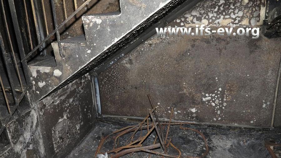 Reste eines verbrannten Kinderwagens unter der Treppe im Erdgeschoss