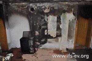 An der Wand ist ein Brandtrichter zu erkennen, an dessen Fußpunkt der Ölofen steht.