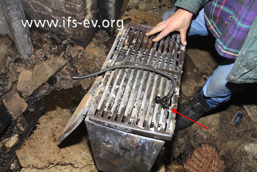 Im Brandschutt findet der Gutachter eine flexible Ölleitung, an deren Ende ein T-Stück montiert ist.
