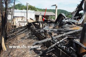 Die Halle ist niedergebrannt. Der Pfeil markiert die Stelle, an der die Maschine steht.