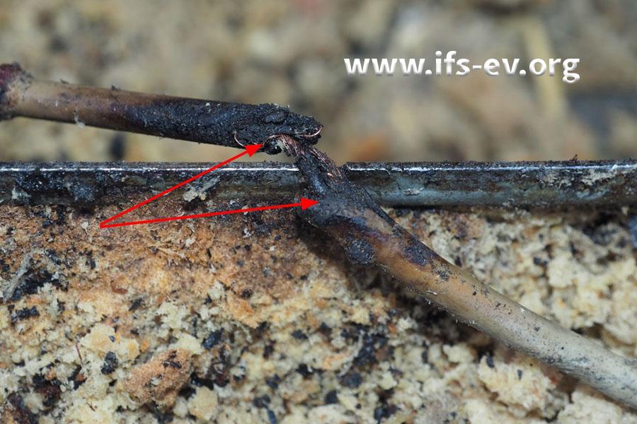 An dieser Stelle liegt eine Leitung über dem Metallprofil des Kanals. Zwischen den Pfeilen ist die Isolation verbrannt.