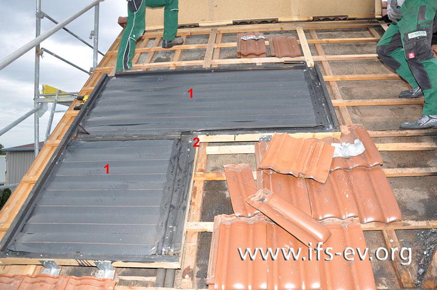 Eine Solaranlage wird demontiert: Das Solarglas wurde bereits entfernt. Darunter sind die Absorberbleche (1) und der schwarz gefärbte Holzrahmen (2) zu sehen.