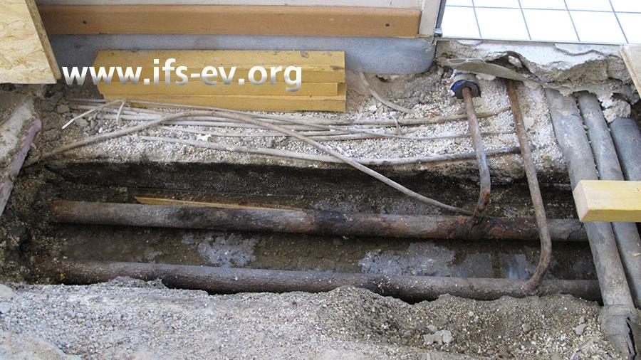 Im unzugänglichen Bodenkanal steht Wasser; die Rohrleitungen sind stark korrodiert.