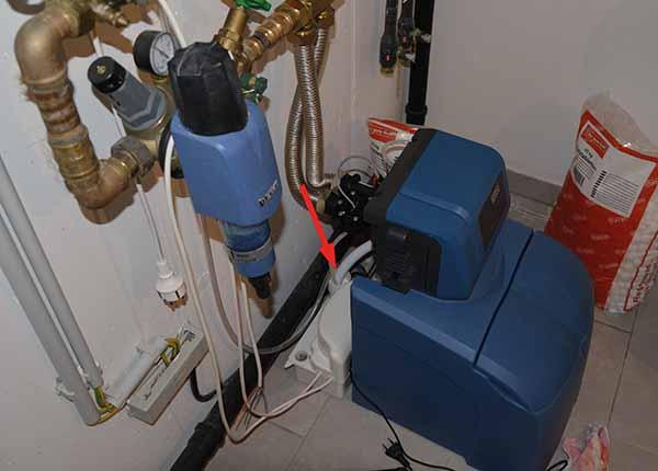 Die Anlage aus einem der beschriebenen Schadenfälle: Der Abfluss der blauen Enthärteranlage ist über eine Art Trichter in die ungeeignete weiße Pumpe geleitet (Pfeil).