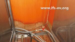 Unter dem Tresen liegen im Bereich der Leckagestelle Feuchteränder am Holz vor. Der Pfeil markiert eine Kernbohrung im Fußboden.