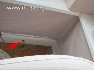 Unter dem Erkerfenster im Wohnzimmer fällt eine korrodierte Befestigungsschraube der Fußleiste auf (Pfeil). Zudem hat sich die Tapete von der Wand gelöst.