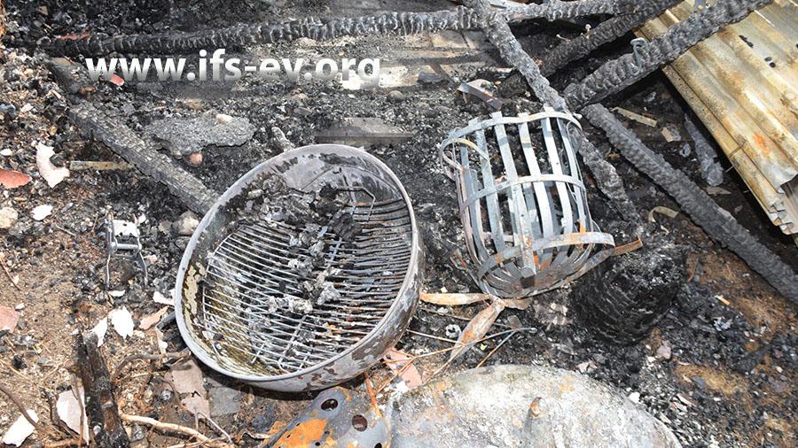 Im Brandschutt liegen ein Grill und der Feuerkorb, in dem das Schwedenfeuer entsorgt wurde.