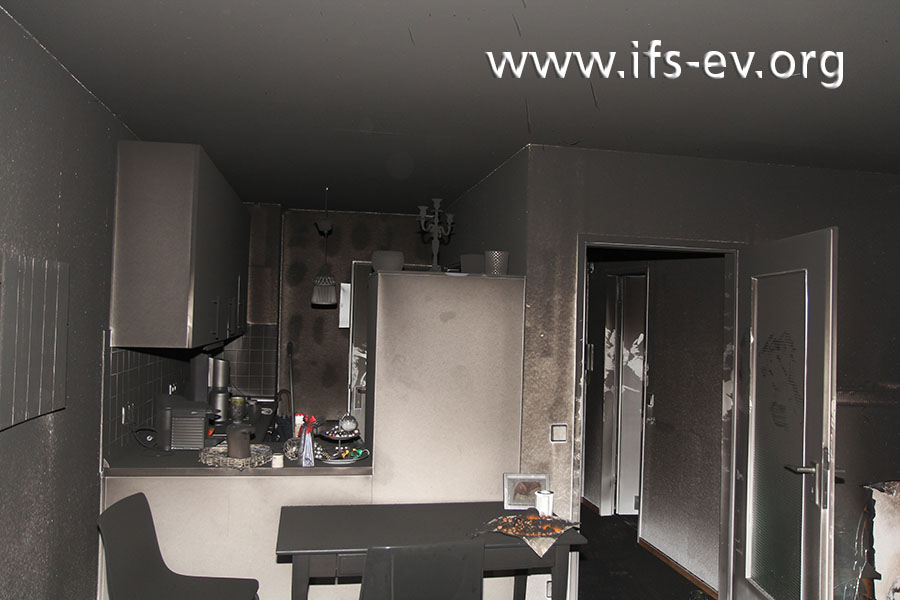 Blick vom Wohnraum in die offene Küche und in den Flur; die ganze Wohnung ist sehr stark durch Ruß verunreinigt.