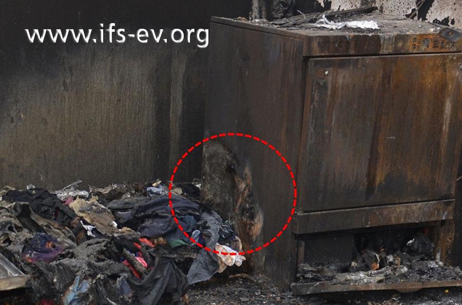 An der Seitenwand des Geschirrspülers fallen sehr starke Brandschäden auf.