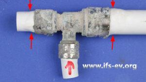 Das T-Stück mit der Undichtigkeit an der markierten Verbindung: Die Rohre sind im Bereich der Druckhülsen aufgequollen (Pfeile).