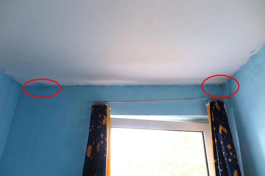 An der Außenwand sind im Anschlussbereich zur Decke dunkle Verfärbungen erkennbar.