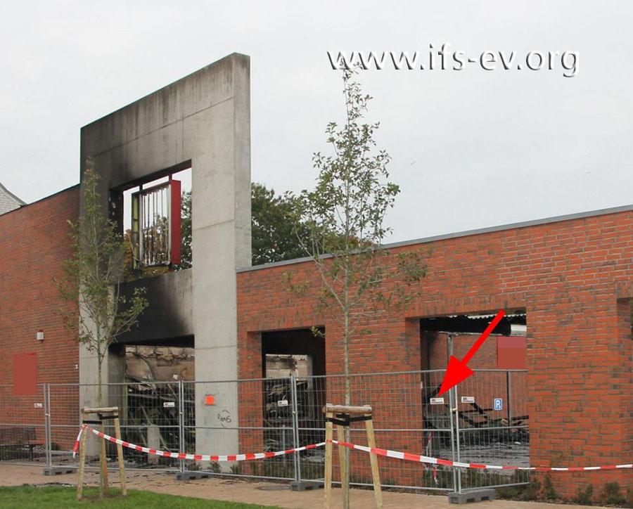 An der verlängerten Front des Gebäudes zeichnet sich eine Rauchgasfahne ab. Dahinter befindet sich der Sammelplatz für die Einkaufswagen (Pfeil).