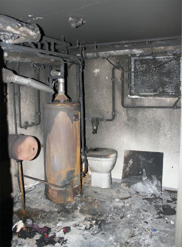Der Warmwasserspeicher im Heizungskeller ist von außen stark beschädigt.