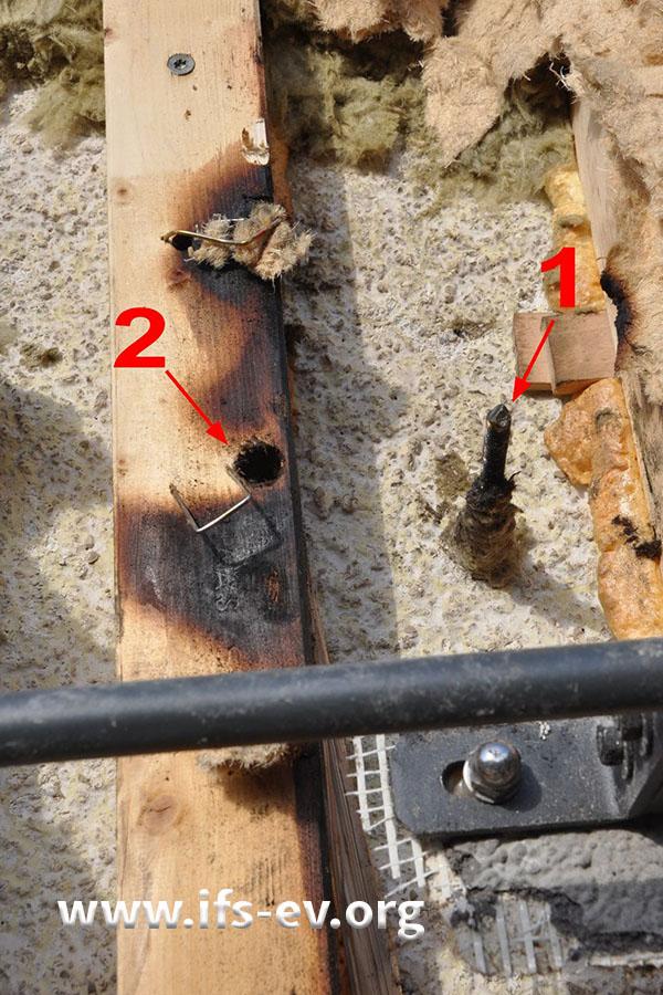 Nahaufnahme des Arbeitsbereiches, in dem eine Schraube abgeflext (1) und in dem Loch links daneben (2) eine neue eingeschraubt wurde.
