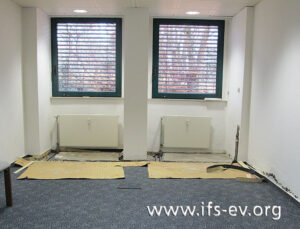 Im Sozialraum wurde der Fußboden geöffnet, und an der Wand ist Schimmelpilzbefall zu erkennen.