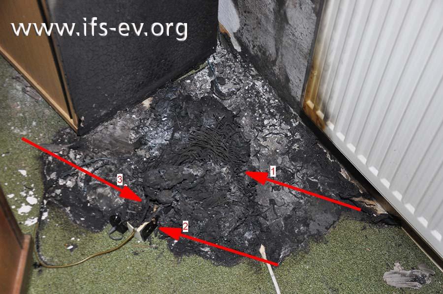Im Brandschutt liegen die Reste einer Dreifachsteckdose unter dem verbrannten Papierkorb.