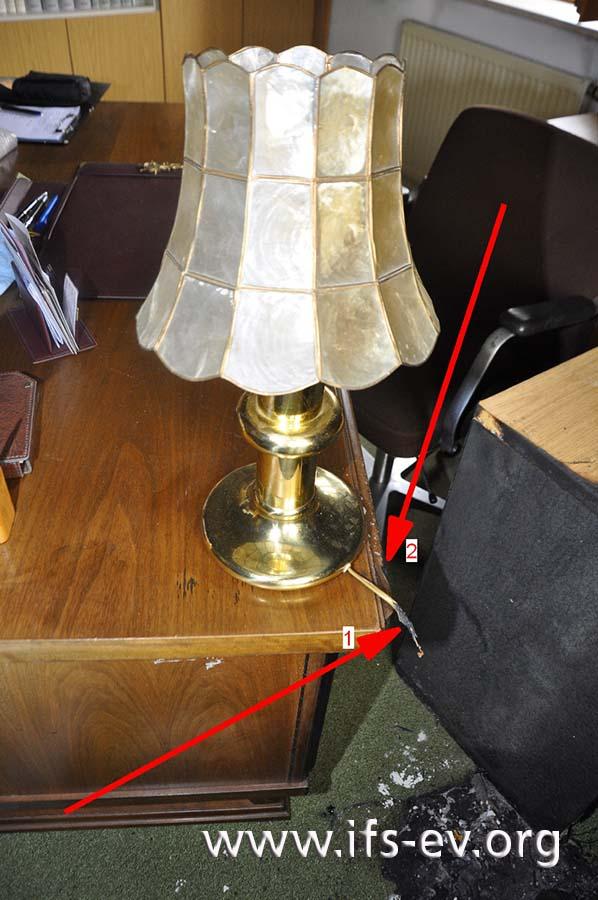 Die Anschlussleitung der Lampe ist durchtrennt (1), und am Schreibtisch gibt es eine kleine Einbrennung (2).