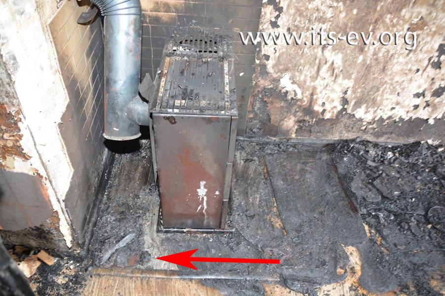 Hinter dem Ölofen klebt eine Kunststoffschmelze auf dem Fußboden.