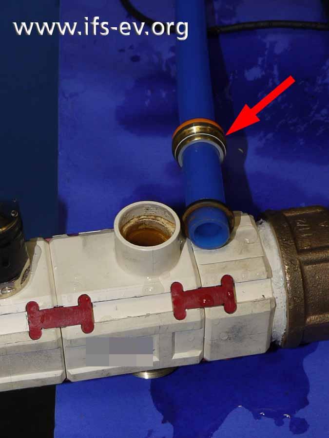 Die Messingsteckhülse (Pfeil) hat sich gelöst, und das Rohr ist aus dem Verteiler aus weißem Kunststoff gerutscht.