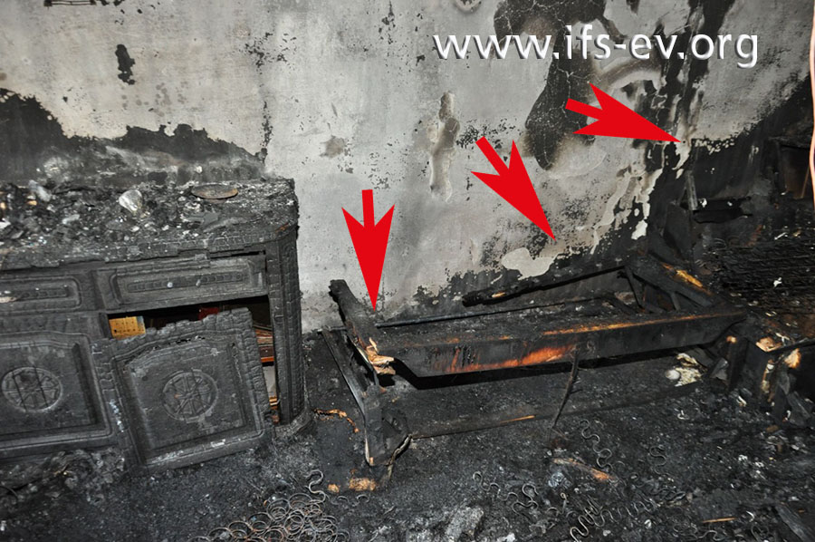 Die Reste des Sofas wurden wieder an ihren ursprünglichen Platz gestellt. Dahinter zeichnet sich an der Wand ein Brandtrichter ab (Pfeile).
