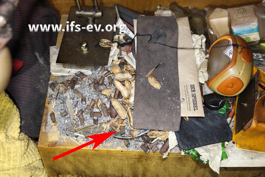 Im Schlafzimmer ist der Aschenbecher auf dem Nachttisch neben dem Bett unter seiner Füllung kaum noch zu erkennen.