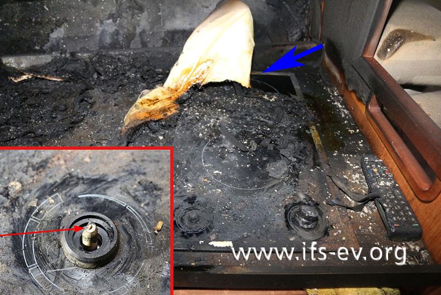 Die Achse des Drehschalters (kleines Bild) belegt, dass die vordere Kochplatte eingeschaltet war. Auf dem Kochfeld klebt Polstermaterial (blauer Pfeil).