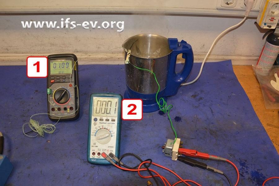 Der Sicherheitstemperaturbegrenzer wird im Labor geprüft: Die Wassertemperatur beträgt 100 °C (1); der Kontakt am STB ist noch immer geschlossen, wie der  gemessene Widerstand von 0,1 Ohm (2) zeigt.