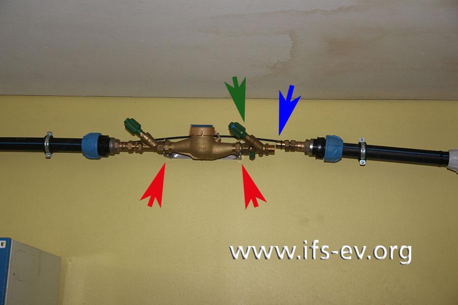 Die roten Pfeile markieren den Wasserzählerbügel. Die getrennte Stelle (blauer Pfeil) hätte innerhalb des Bügels liegen sollen. Außerhalb des Zählerbügels waren die beiden Ventile anzuordnen, wobei das grün markierte KFR-Ventil links des Bügels auf der Ausgangsseite zu installieren gewesen wäre.