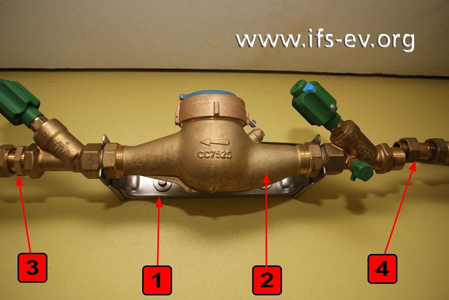 Hier ist der Bügel (1) hinter dem Wasserzähler (2) gut zu erkennen, ebenso wie die Eingangsverschraubung (3) und die Längenausgleichsverschraubung (4). Die Fließrichtung des Wassers erfolgt von rechts (Eingangsseite) nach links (Ausgangsseite).