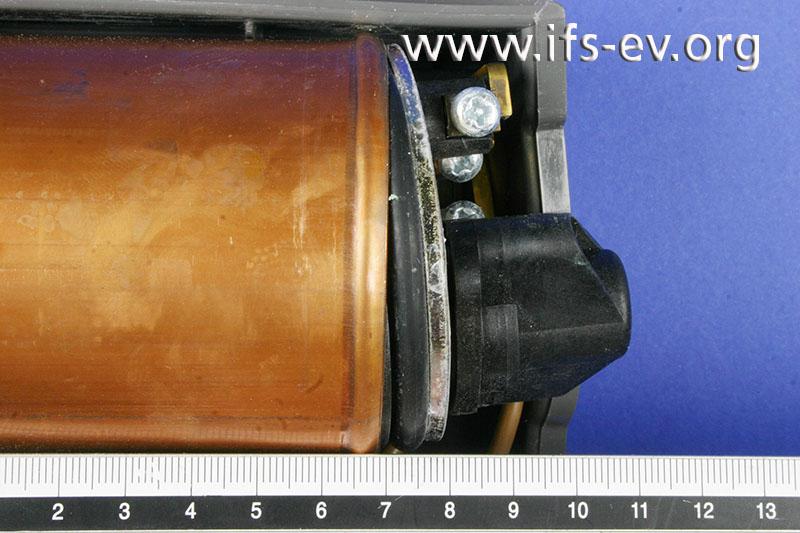An einer Seite ist die Sitzplatte etwa einen Zentimeter aus der Umbördelung der Patrone gedrückt worden.