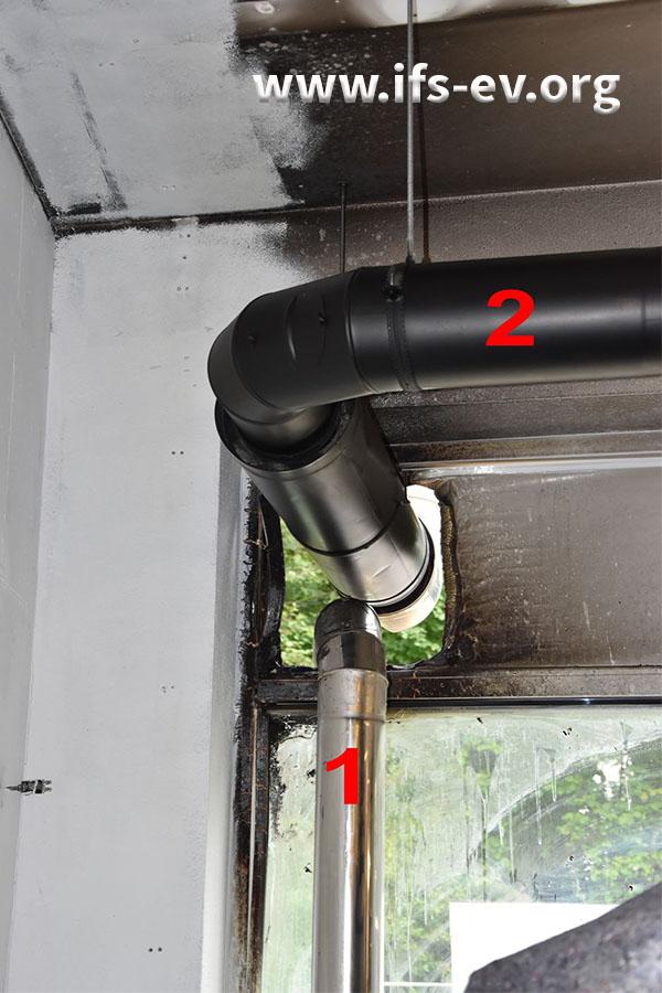 Die Rohre für die Abluft des Kühlers (1) und aus der Rösttrommel (2)  werden durch ein Kunststoffelement der Fensterfront nach außen geführt. Um die Rohre herum ist der Kunststoff angeschmolzen.