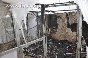 Ein Blick in den ausgebrannten Stall; im Vordergrund sieht man die geschmolzene Kunststoff-Folie herunterhängen.