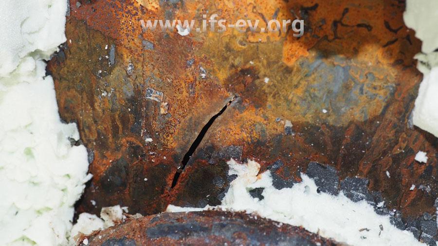 Dort ist hinter der Isolierung die Behälterwand gerissen und nach außen gewölbt.