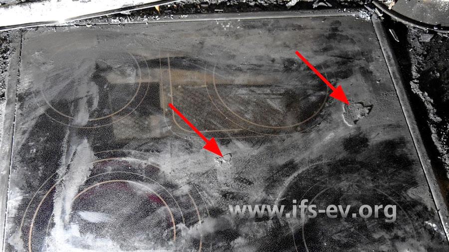 An zwei Stellen sind verkohlte Teile auf dem Ceranfeld festgebacken (Pfeile).