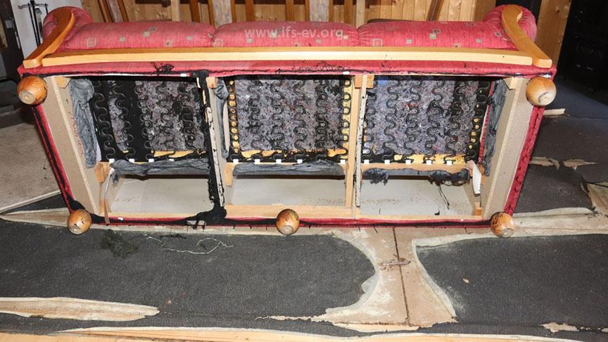An der Unterseite des Sofas und am Fußbodenbelag gibt es thermische Schäden.