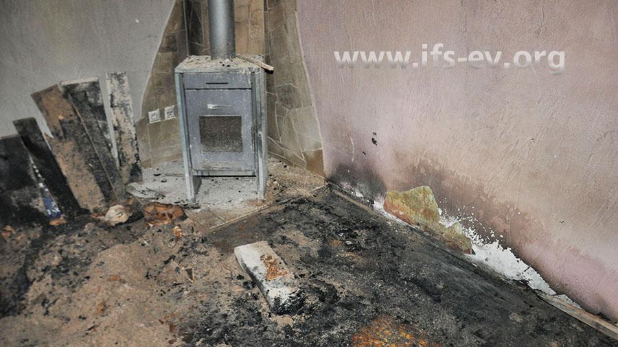 Rechts des Ofens ist der Bodenbelag am stärksten verbrannt.