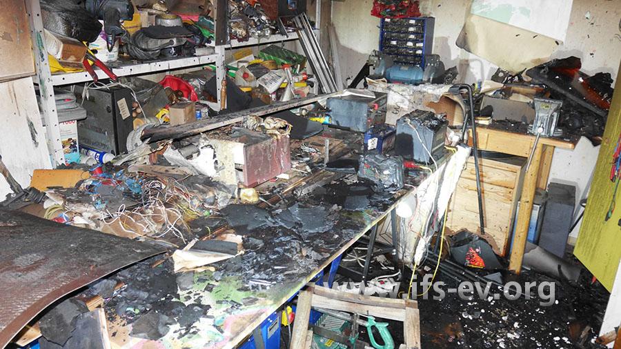 Die Gegenstände auf der Werkbank sind lediglich angeschmolzen. Darauf liegen verbrannte Reste der Deckenpaneele.