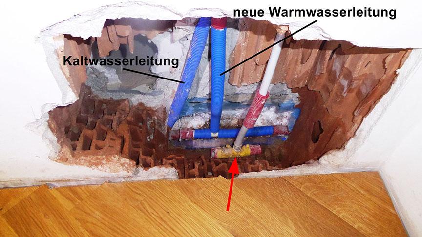 Bild von der Baustelle: Das schadenursächliche T-Stück (Pfeil) wurde zum Vergleich lose wieder eingebracht. Die neue (reparierte) Warmwasserleitung mit rechtwinkligem Abzweig und die alte Kaltwasserleitung in der ursprünglichen Position mit verbogenem Abzweig.