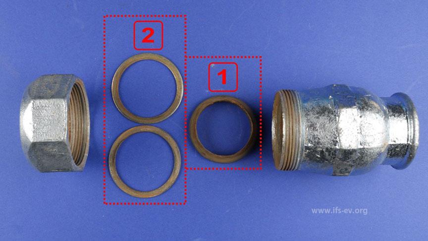 Der Verbinder wird in seine Einzelteile zerlegt: Im Inneren des Überwurfes sind ein konusförmiges Dichtelement aus Kunststoff [1] und zwei Unterlegscheiben aus Stahl [2] vorhanden. Es fehlt der Klemmring.
