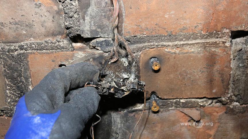 Die Netzleitung der Mehrfachsteckdose (Pfeil) ist noch an die Reste einer Wandsteckdose angeschlossen.
