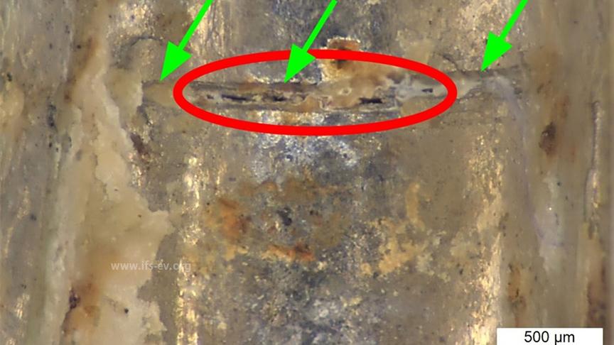 """In einem """"Wellental"""" befindet sich ein feiner Riss (rote Markierung) direkt in einer der beiden Längsriefen (grüne Pfeile)."""