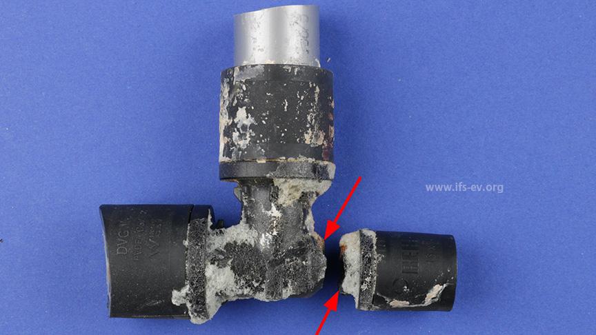 An dem Fittinggrundkörper haften Reste von Bauschaum - auch im Bereich des Bruches (Pfeile).