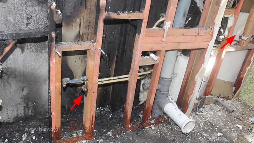 Am Holz der Wandkonstruktion gibt es an mehreren Stellen auffälligen Brandspuren (Pfeile).