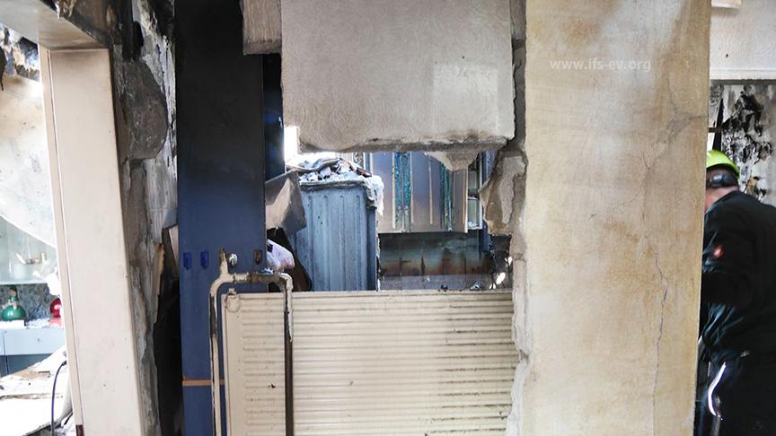 Blick vom Flur durch die zum Teil eingebrochene Wand auf die Rückseite des Heizkörpers und in das Badezimmer