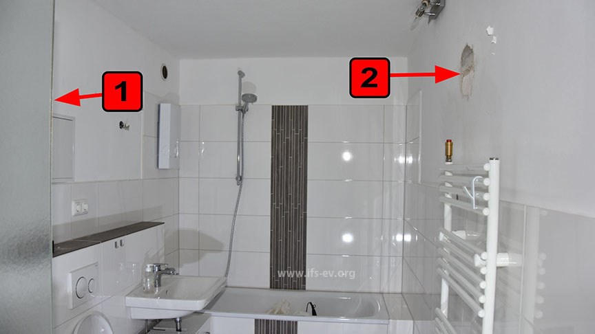 Derselbe Raum ein halbes Jahr später: An der Markierung 1 war das Wasser aus der Wand ausgetreten und hatte bei Markierung 2 den Wandputz ausgespült.
