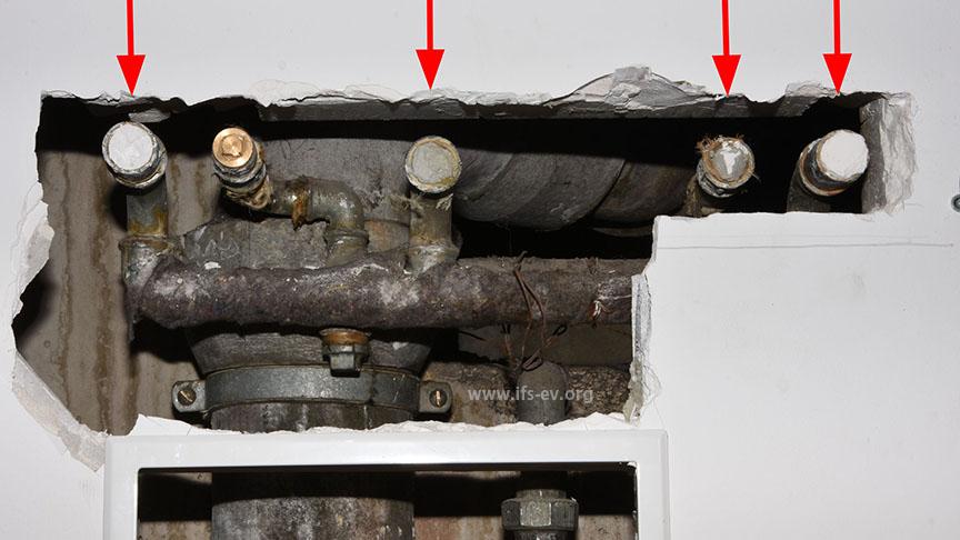 Nach dem Öffnen der Wand werden fünf Anschlüsse sichtbar, die mit Spachtel verschlossen waren. Am zweiten von links (hier mit Messingstopfen) war das Wasser ausgetreten.